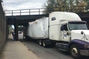 A tractor-trailer is trapped under a bridge on Robinson Street